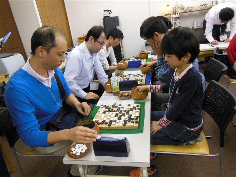 手前は下のクラスの決勝戦。その奥に元アマチュア本因坊の村上深さん(左から二人目)の姿も見えます。