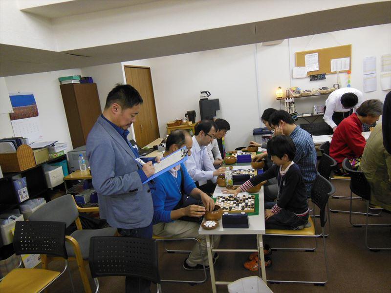 下のクラスの決勝の碁を、主催の政光順二氏が棋譜付けしているというシーン。手作りの大会ならではの光景です。